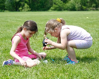 Sisters Mia Niznik, 6, left, and Maylee Niznik, 4, both of Struthers, look for flowers and bugs at Kids to Parks Day at Ipe Field on Saturday afternoon. EMILY MATTHEWS | THE VINDICATOR