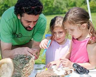 Josh Boyle, left, of Boardman and with Environmental Collaborative of Ohio, looks at flowers found by sisters Maylee Niznik, 4, center, and Mia Niznik, 6, both of Struthers, at Kids to Parks Day at Ipe Field on Saturday afternoon. EMILY MATTHEWS | THE VINDICATOR