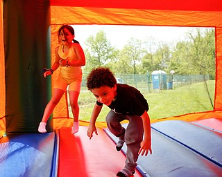 Mya Niznik, 6, of Struthers, left, and Noah Axel, 3, of Poland, play in a bounce house at Kids to Parks Day at Ipe Field on Saturday afternoon. EMILY MATTHEWS | THE VINDICATOR