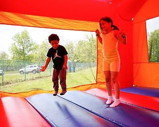 Noah Axel, 3, of Poland, left, and Mya Niznik, 6, of Struthers, play in a bounce house at Kids to Parks Day at Ipe Field on Saturday afternoon. EMILY MATTHEWS | THE VINDICATOR