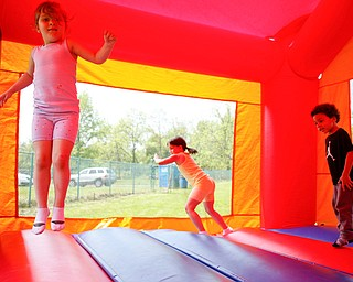 From left, Maylee Niznik, 4, Mya Niznik, 6, both of Struthers, and Noah Axel, 3, of Poland, play in a bounce house at Kids to Parks Day at Ipe Field on Saturday afternoon. EMILY MATTHEWS | THE VINDICATOR