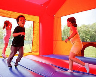 From left, Maylee Niznik, 4, of Struthers, Noah Axel, 3, of Poland, and Mya Niznik, 6, of Struthers, play in a bounce house at Kids to Parks Day at Ipe Field on Saturday afternoon. EMILY MATTHEWS | THE VINDICATOR