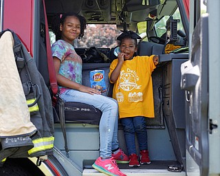 Traeh Lewis, 11, left, and Minnie Smith, 6, eat potato chips in the front of a Youngstown firetruck at Kids to Parks Day at Ipe Field on Saturday afternoon. EMILY MATTHEWS | THE VINDICATOR