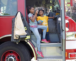 Traeh Lewis, 11, left, and Minnie Smith, 6, both of Youngstown, eat potato chips in the front of a Youngstown firetruck at Kids to Parks Day at Ipe Field on Saturday afternoon. EMILY MATTHEWS | THE VINDICATOR