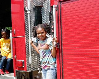Traeh Lewis, 11, of Youngstown, right, stands on the side of a Youngstown firetruck while Minnie Smith, 6, of Youngstown, sits inside at Kids to Parks Day at Ipe Field on Saturday afternoon. EMILY MATTHEWS | THE VINDICATOR