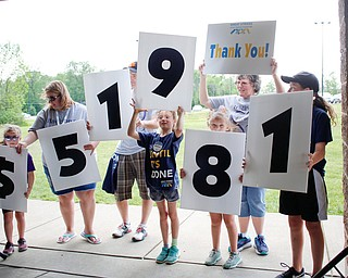 From left, Madison Himes, 6, who has cystic fibrosis, Maggie Himes, John Himes, Aislynn Himes, 8, all of New Middletown, Tessa Carrabbia, 8, of Austintown, Claudia Mehocic, of Pulaski, and Melina Carrabbia, 11, of Austintown, hold up signs that read $51,981, which is how much money was raised during the 20th annual Mahoning/Trumbull Great Strides cystic fibrosis walk at Boardman Park on Sunday afternoon. EMILY MATTHEWS   THE VINDICATOR