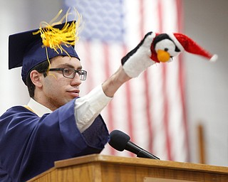 Alex Giovannone uses hand puppets in his valedictorian speech during the Austintown Fitch commencement ceremony in the school's gymnasium Saturday morning. EMILY MATTHEWS | THE VINDICATOR