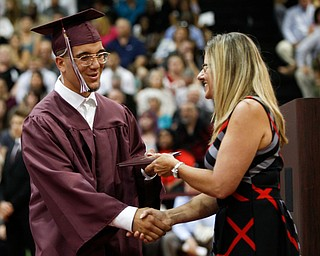 Edwin Cortes receives his diploma from Boardman Board of Education Vice President Victoria Davis during Boardman's commencement ceremony in the school's gym on Sunday afternoon. EMILY MATTHEWS | THE VINDICATOR