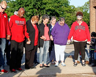 People who are gathered for a vigil to honor Brad and Jacob Crist, who died in a house fire in Niles last week, bow their heads during a prayer at the Niles Safety-Service Complex on Sunday evening. EMILY MATTHEWS | THE VINDICATOR