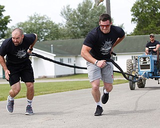 Chuck Lengyel, left, and Nathan Daniszewski, both with Drayer Physical Therapy, participate in a people-powered tractor pull during the Autism Warrior Event at the Canfield Fairgrounds on Saturday. EMILY MATTHEWS   THE VINDICATOR