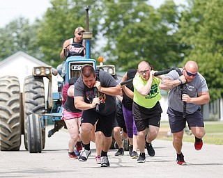 From left, Anthony Lariceia, Adam Miller, and Nick Franceschelli, all with Team BSS Training and Fitness, lead their team in a people-powered tractor pull during the Autism Warrior Event at the Canfield Fairgrounds on Saturday. EMILY MATTHEWS   THE VINDICATOR