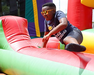 Miciah Lampley, 9, of Warren, plays on an inflatable obstacle course during the Autism Warrior Event at the Canfield Fairgrounds on Saturday. EMILY MATTHEWS   THE VINDICATOR