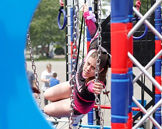 Kamryn Long, 17, grabs a swing on the ninja obstacle course during the Autism Warrior Event at the Canfield Fairgrounds on Saturday. She completed the course with her twin sister Reygan, both of whom have autism and cheer with Miss Dana's Diamonds. EMILY MATTHEWS   THE VINDICATOR