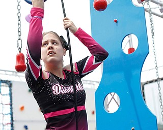 Kamryn Long, 17, grabs a ring to pull herself up in a ninja obstacle course during the Autism Warrior Event at the Canfield Fairgrounds on Saturday. She completed the course with her twin sister Reygan, both of whom have autism and cheer with Miss Dana's Diamonds. EMILY MATTHEWS   THE VINDICATOR