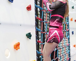Reygan Long, 17, climbs on a rope and rock wall, part of a ninja obstacle course, during the Autism Warrior Event at the Canfield Fairgrounds on Saturday. She completed the course with her twin sister Kamryn, both of whom have autism and cheer with Miss Dana's Diamonds. EMILY MATTHEWS   THE VINDICATOR