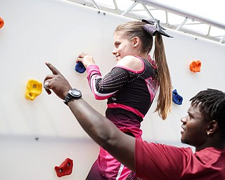 Reygan Long, 17, climbs on a rock wall, part of a ninja obstacle course, with help from Travon Herst, with A&S Party Rental, during the Autism Warrior Event at the Canfield Fairgrounds on Saturday. She completed the course with her twin sister Kamryn, both of whom have autism and cheer with Miss Dana's Diamonds. EMILY MATTHEWS   THE VINDICATOR