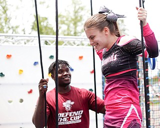 Reygan Long, 17, participates in a ninja obstacle course, with help from Travon Herst, with A&S Party Rental, during the Autism Warrior Event at the Canfield Fairgrounds on Saturday. She completed the course with her twin sister Kamryn, both of whom have autism and cheer with Miss Dana's Diamonds. EMILY MATTHEWS   THE VINDICATOR