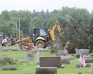 ROBERT K.YOSAY  | THE VINDICATOR..People from Warren to Brookfield are cleaning up after SundayÕs damaging winds after learning that the mess indeed was created by a tornado and possibly a series of touchdowns...trees toppled and headstones knocked down at Brookfield Cemetery- workers use a backhoe to move trunks of trees
