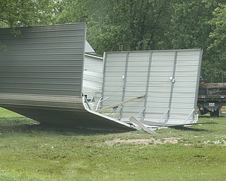 ROBERT K.YOSAY  | THE VINDICATOR..People from Warren to Brookfield are cleaning up after SundayÕs damaging winds after learning that the mess indeed was created by a tornado and possibly a series of touchdowns...a portable car port on Templeton Rd NW  was overturned