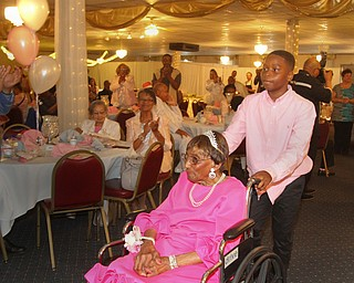 William D. Lewis The Vindicator Rev. Flonerra Henry-Harris makes a grand entrance at the Mahoning Country Club where a 100th birthday party was held for her 6-21-19. She is escorted by one of er great grandsons Mekher Madison, 11, of Streetsboro.