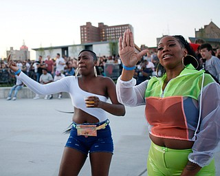 Angela Wagner, left, and Alveta Burgess, both of Youngstown, dance before Gucci Mane took the stage at the Youngstown Foundation Amphitheatre on Saturday. EMILY MATTHEWS | THE VINDICATOR