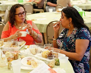 Cynthia Williams, left, and Sarah Cruz-Banks, both of Youngstown, try food from different cooks during Taste of St. Patrick's at St. Patrick Church of Youngstown on Sunday. EMILY MATTHEWS | THE VINDICATOR