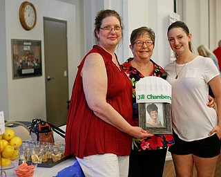 From left, Jill Chambers, her mother Nancy Chambers, and her daughter Teryn Ross, all of Boardman, pose with a photo of Nancy's mother Elaine, whose fluff recipe they use, during Taste of St. Patrick's at St. Patrick Church of Youngstown on Sunday. EMILY MATTHEWS | THE VINDICATOR