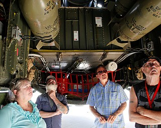 From left, Christine Cummings, of Warren, Shawn Smith, of Cincinnati, Mark Fontanarosa, of Warren, and Richard Phillips, of Warren, look under a B-29 at the Warren Regional Airport on Wednesday. EMILY MATTHEWS | THE VINDICATOR