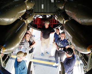 A tour group learns about the B-29 they're standing under at the Warren Regional Airport on Wednesday. The B-29 and an AT6 were at the airport for people to look at and learn about. EMILY MATTHEWS | THE VINDICATOR