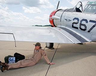 Andy Trevnicek, a volunteer with the Commemorative Air Force and one of the pilots of the Avenger Field AT6 that was flown by the WASPs, sits in the shade under one of the wings of the AT6 at the Warren Regional Airport on Wednesday. The AT6 and a B29 were at the airport for people to look at and learn about. EMILY MATTHEWS | THE VINDICATOR