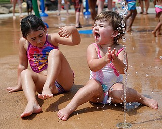 Sisters Scarlett, 1, right, and Riley HIbbird, 4, of Boardman play in the water at the water park in the James L. Wick, Jr. Recreation Area in Mill Creek Park on Thursday. EMILY MATTHEWS   THE VINDICATOR