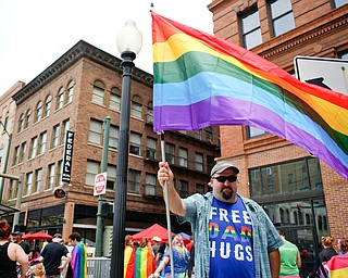 Michael Amedio, of East Liverpool, holds a pride flag and wears a shirt that reads Free Dad Hugs at the 11th annual Pride parade and festival in downtown Youngstown on Saturday afternoon. Amedio said he wore the shirt as a message of support that some people in the LGBTQ do not receive from their parents. EMILY MATTHEWS   THE VINDICATOR