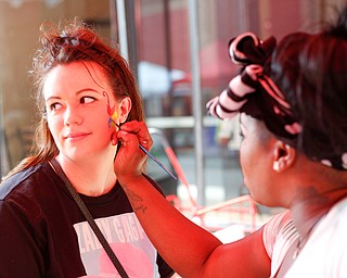 Krystal Adams, of Austintown, left, gets her face painted by Terri Belser, of Terri's Face Painting, at the 11th annual Pride parade and festival in downtown Youngstown on Saturday afternoon. EMILY MATTHEWS   THE VINDICATOR