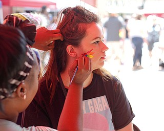 Krystal Adams, of Austintown, gets her face painted by Terri Belser, of Terri's Face Painting, at the 11th annual Pride parade and festival in downtown Youngstown on Saturday afternoon. EMILY MATTHEWS   THE VINDICATOR