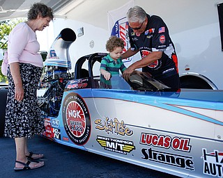 """PDRA world champion Tom Martino, of Youngstown, right, helps Robert """"Obie"""" Alden, 4, of Niles, get into his Top Dragster while Alden's grandmother Patty Butler, of Niles, watches nearby at the Mahoning Valley Corvette Club's 25th Annual Corvette and Steel Car Show at Greenwood Chevrolet in Austintown on Sunday. EMILY MATTHEWS   THE VINDICATOR"""