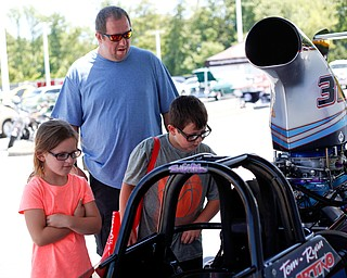 From left, Savannah Thomas, 6, William Thomas, and William Thomas, Jr., all of Boardman, look at PDRA world champion Tom Martino's Top Dragster at the Mahoning Valley Corvette Club's 25th Annual Corvette and Steel Car Show at Greenwood Chevrolet in Austintown on Sunday. EMILY MATTHEWS   THE VINDICATOR
