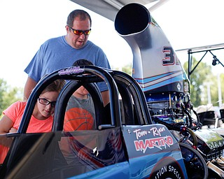 Savannah Thomas, 6, looks at PDRA world champion Tom Martino's Top Dragster with her dad William Thomas and brother William Thomas, Jr., all of Boardman, at the Mahoning Valley Corvette Club's 25th Annual Corvette and Steel Car Show at Greenwood Chevrolet in Austintown on Sunday. EMILY MATTHEWS   THE VINDICATOR
