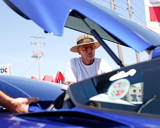 Elmer Swearingen, of New Cumberland, West Virginia, prepares to put the roof on his 2017 Corvette Grand Sport with help from Rex Swortzbeck, left, of Greenville, Pa., at the Mahoning Valley Corvette Club's 25th Annual Corvette and Steel Car Show at Greenwood Chevrolet in Austintown on Sunday. EMILY MATTHEWS   THE VINDICATOR
