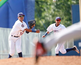 Scrappers' Jonathan Lopez, left, throws the ball to first during their game against the Muckdogs at Eastwood Field on Sunday afternoon. EMILY MATTHEWS | THE VINDICATOR
