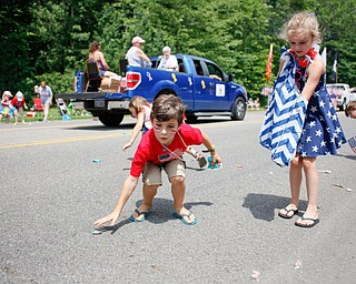 Cousins Anthony Miller, 8, of Austintown, left, and Tayla Price, 9, of Warren, pick up candy during the Austintown Fourth of July parade on Raccoon Road Thursday afternoon. EMILY MATTHEWS | THE VINDICATOR