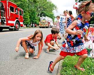 Alexis Price, 4, of Warren, right, picks up candy with her cousins Lena Miller, 6, left, and Anthony Miller, 8, both of Austintown, during the Austintown Fourth of July parade on Raccoon Road Thursday afternoon. EMILY MATTHEWS | THE VINDICATOR