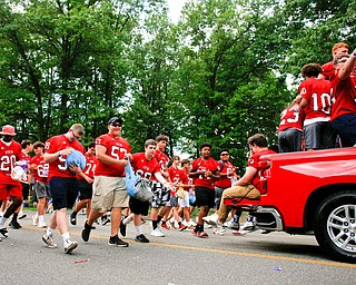 Austintown Fitch football players toss candy during the Austintown Fourth of July parade on Raccoon Road Thursday afternoon. EMILY MATTHEWS | THE VINDICATOR