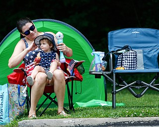 Ashley Hohos, of Austintown, adjusts her 15-month-old daughter Gabrianna Hohos' hat as they watch the Austintown Fourth of July parade on Raccoon Road Thursday afternoon. EMILY MATTHEWS | THE VINDICATOR