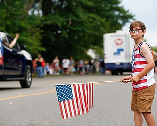 Dominic Miller, 9, of Austintown, watches the Austintown Fourth of July parade on Raccoon Road Thursday afternoon. EMILY MATTHEWS | THE VINDICATOR