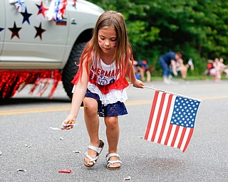 Lena Miller, 6, of Austintown, picks up candy during the Austintown Fourth of July parade on Raccoon Road Thursday afternoon. EMILY MATTHEWS | THE VINDICATOR