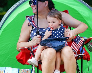 Gabrianna Hohos, 15 months, eats lollipops while sitting on the lap of her mom Ashley Hohos, of Austintown, as they watch the Austintown Fourth of July parade on Raccoon Road Thursday afternoon. EMILY MATTHEWS | THE VINDICATOR