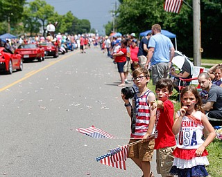 From left, siblings Dominic Miller, 9, Anthony Miller, 8, and Lena Miller, 6, all of Austintown, watch the Austintown Fourth of July parade on Raccoon Road Thursday afternoon. EMILY MATTHEWS | THE VINDICATOR