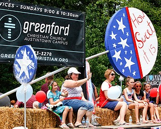 People with Greenford Christian Church wave and ride in the Austintown Fourth of July parade on Raccoon Road Thursday afternoon. EMILY MATTHEWS | THE VINDICATOR
