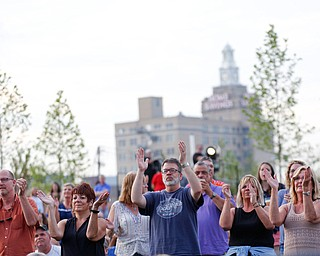 People in the crowd clap along as Earth, Wind & Fire perform at the Youngstown Foundation Amphitheatre Friday night. EMILY MATTHEWS | THE VINDICATOR