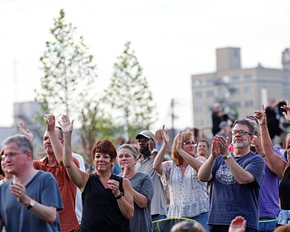 People in the crowd clap and dance as Earth, Wind & Fire perform at the Youngstown Foundation Amphitheatre Friday night. EMILY MATTHEWS | THE VINDICATOR